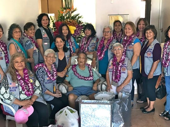 """Members of the Guam Sunshine Lions Club and the Guam Tano'Ta Branch Club visited Antonio L. G. Okiyama, 86, (seated,  4th from left) at his residence in Yona on March 17.  In conjunction with its community service mission of """"Caring for the Sick and the Elderly,"""" members brought supplies, song, and cheer.  In celebration of Mes Chamoru, Lion Pilar Laguana, (standing 5th from left) presented a fresh flower arrangement to Okiyama and his family, and orchid leis to the Lion members. Seated from left: Lions LouJean Borja, Jovie Mejorada, and Herdie Dela Cruz;  Okiyama; and Lion Helen Mendiola. Standing l to r: Lions Pete Babauta, Marietta Camacho, Dot Leon Guerrero, Dee Cruz, Pilar Laguana, Julie Garcia, Connie Rivera, Helen Colby, Tish Tano, Julie Cruz, Clarice Quichocho, Mary Taitano, Linda Villagomez, Sophie Losongco, and Johnny Villagomez (Guam Tano'Ta Branch Club)."""