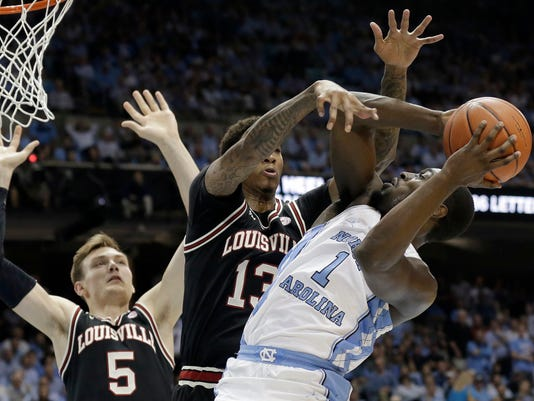 North Carolina's Theo Pinson (1) drives to the basket while Louisville's Ray Spalding (13) and Matz Stockman (5) defend during the first half of an NCAA college basketball game in Chapel Hill, N.C., Wednesday, Feb. 22, 2017. (AP Photo/Gerry Broome)