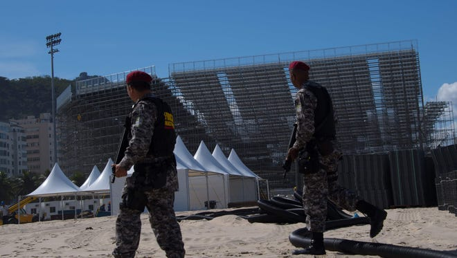 Policemen patrol the surroundings of the beach volleyball stadium structure which will host the Olympic competition, at Copacabana beach in Rio de Janeiro on July 8.
