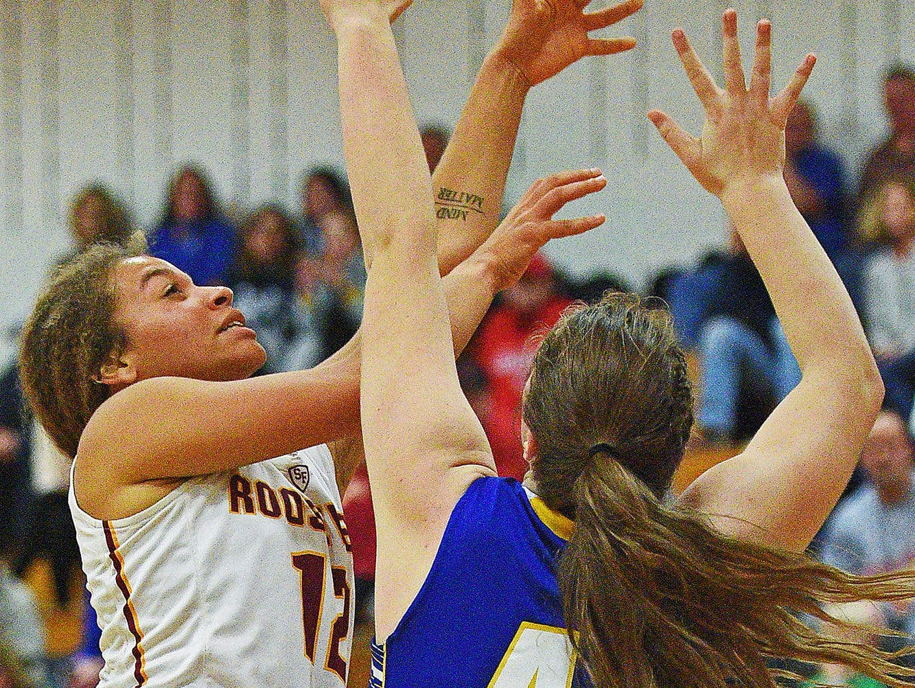 Roosevelt's Kira Ward (12) takes a shot as O'Gorman's Courtney Baruth (41) defends during a game Friday, Dec. 9, 2016, at Roosevelt High School in Sioux Falls.