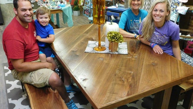 Ben Crawford and son, Jack, sit on a bench, left, and Wendy Brown, back right, and her daughter Amanda, right, gather at the black walnut table Crawford donated for a raffle this month.