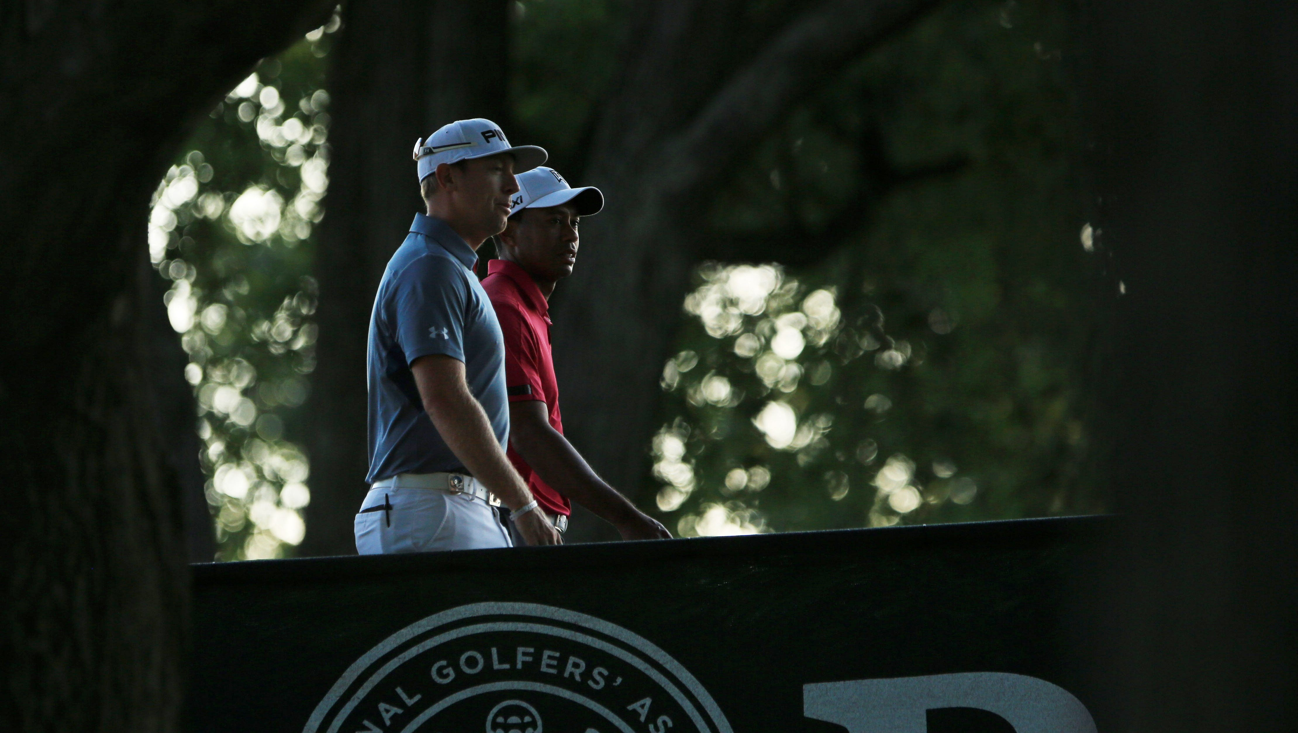 Tiger Woods and Hunter Mahan walk to play their practice round for the 95th PGA Championship at Oak Hill Country Club.