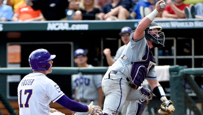TCU catcher Evan Skoug, right, holds up the ball after tagging out LSU second baseman Jared Foster (17) in the third inning of an NCAA College World Series baseball game at TD Ameritrade Park in Omaha, Neb., Sunday, June 14, 2015.  (AP Photo/Mike Theiler)