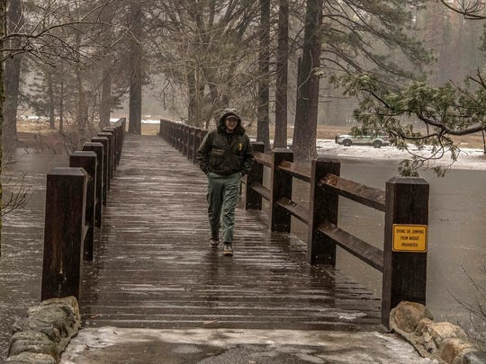 Park service workers check out a swinging bridge along