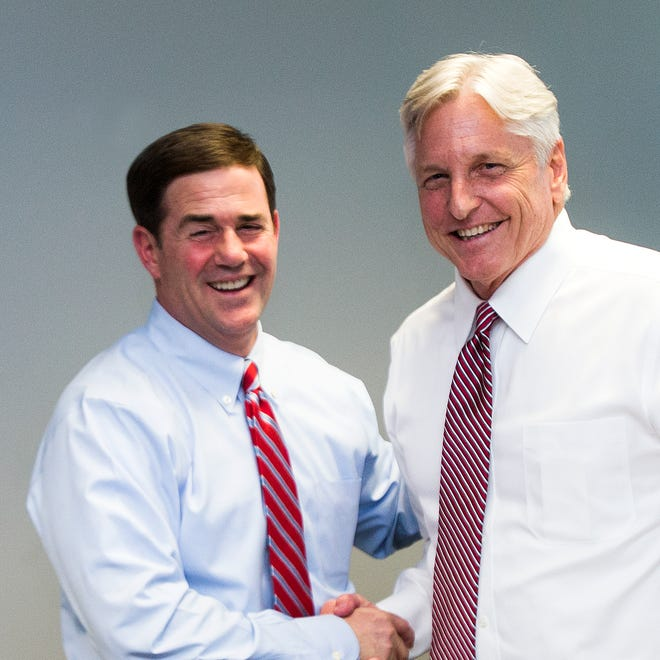 Republican Doug Ducey, left, and Democrat Fred DuVal, middle, candidates for Governor, greet each other after meeting with John Zidich, right, and  the Arizona Republic editorial board on Wednesday, October 1, 2014.