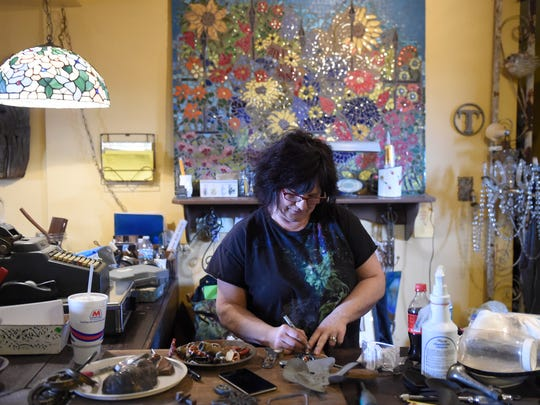Salvage Candy owner Tammy Trem marks items while working at the business on S. Weinbach Ave., in Evansville recently.  The business specializes in selling vintage items that many customers use to make new creations.