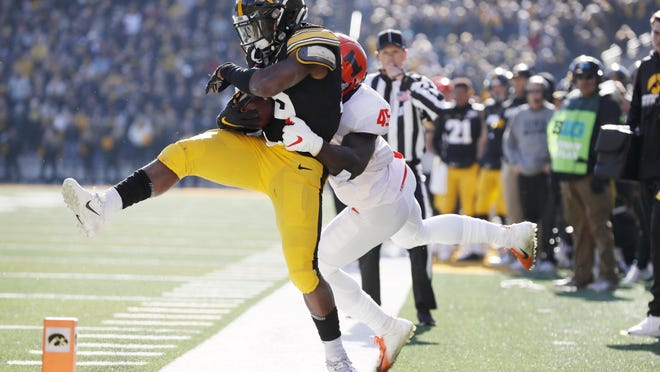Iowa running back Tyler Goodson is forced out of bounds by Illinois linebacker Khalan Tolson, right, during the first half on Nov. 23, 2019, in Iowa City, Iowa. Iowa won 19-10.