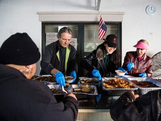 From left: volunteers Richard Sapia, Mia Sallade and Jackie Sallade serve a hot meal during lunch at Justin's Place Feeding Ministry in East Naples on Thursday, Jan. 4, 2018.