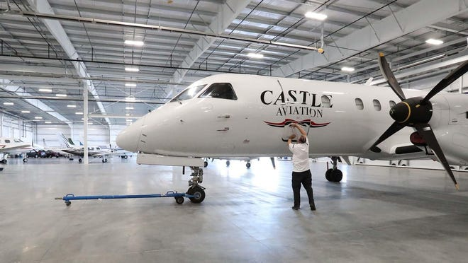 Michael Grossmann, the owner of Castle Aviation, closes the door to one of his fleet's freight planes Friday in the company's new hangar at the Akron-Canton Airport.