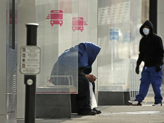 People wait for a bus Tuesday in a mostly deserted downtown Kansas City as stay-at-home orders continue in much of the country in an effort to stem the spread of the coronavirus.