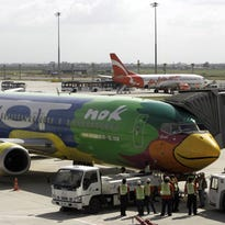 Ground staff check passenger planes of Nok Air, front, and AirAsia, rear, at Bangkok's international airport in this file photo from July 29, 2006.