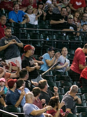 Fans react to a bat accidentally tossed into the stands at the Diamondbacks game on Thursday, Sept. 17, 2014, in Phoenix against the Giants.