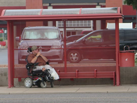 A resident waits for the bus at a stop along the 700
