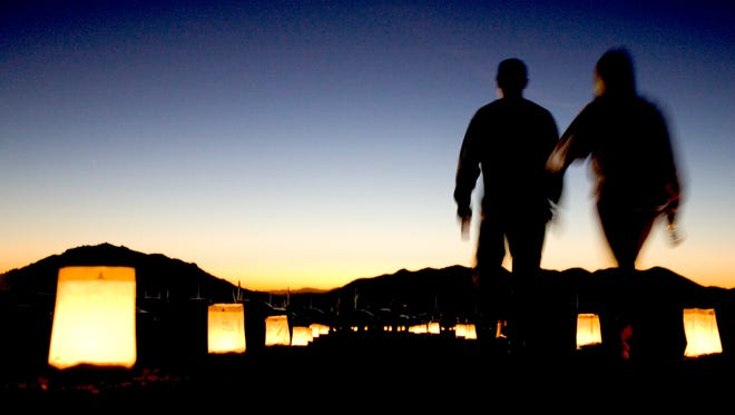 A couple walks along a path lined with luminarias during the Cave Creek Luminaria Run.