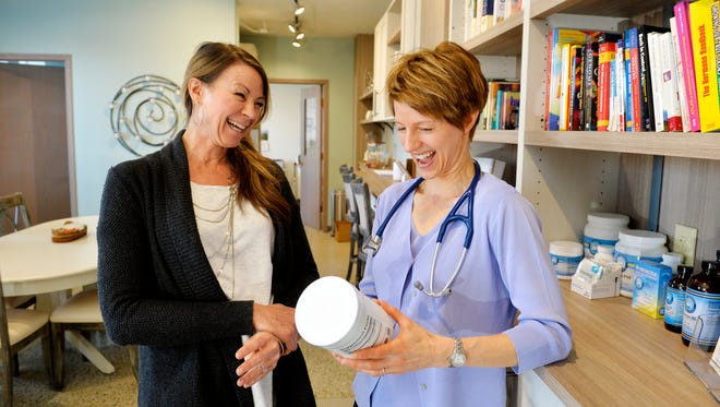 Michelle Schunzel, left, a health and nutrition coach, assists Dr. Loy Anderson, right, in treating patients at Thriven Functional Medicine Clinic in the Columbus Center.