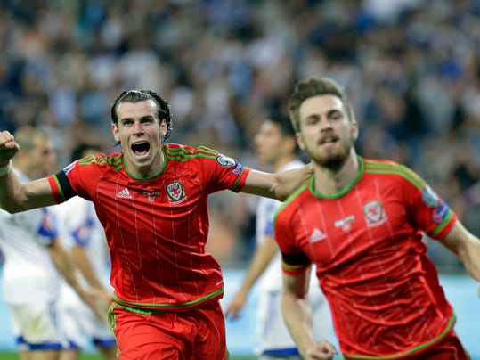 FILE - In this Saturday, March 28, 2015 file photo, Wales' Aaron Ramsey, right and Gareth Bale celebrate after they scored against Israel during the Euro 2016 qualifying group B soccer match in Haifa, Israel.  At the 2018 World Cup qualifying draw on Saturday, July 25, 2015, two European countries could be rewarded for perfect tactics on and off the field, where both Romania and Wales should be top-seeded in their groups despite not playing at a World Cup for decades. (AP Photo/Dusan Vranic, FILE)