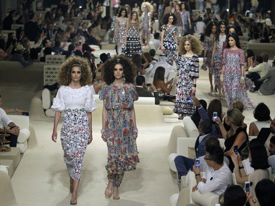 In this May 2014 photo, models walk among the guests at the Chanel Cruise Dubai show revealing the French Maison's new Cruise collection for the 2014-15 season, staged on a private island in Dubai, United Arab Emirates.