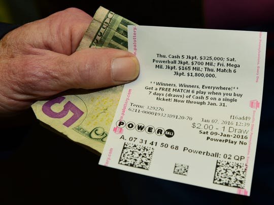 Francis Cameron holds a  Powerball ticket he purchased Thursday afternoon, Jan. 7, 2016, at Bill's Kwik Chek, Lincoln Way West, Chambersburg. The jackpot early afternoon reached $700 million.