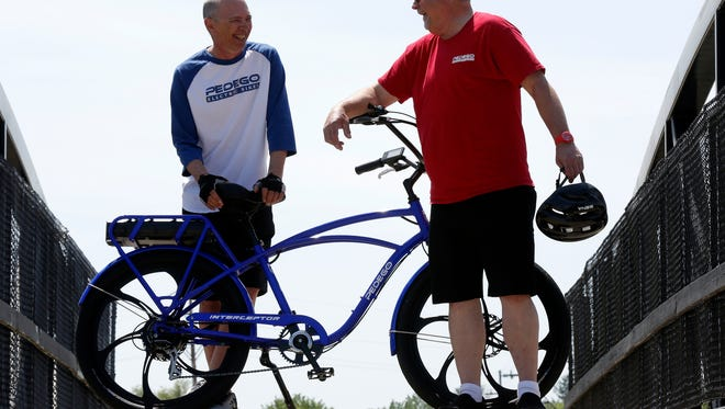 (L to R) Jay Hoopingarner and Greg Krzeminski, who is the owner of Pedego Junction Electric Bikes in Harrison Township with their Pedego e-bikes on the Larry Obrecht bridge at the Polly Ann Trail pedestrian overpass bridge on Thursday, May 24, 2018 in Oxford, Michigan.Hoopingarner has Parkinson's Disease and is worried about various trails that ban motored bikes like his. The e-bike allows him to ride in what would be a hard effort on a regular bike as he deals with Parkinson's.