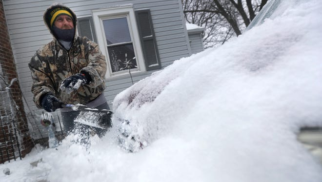 John Busse clears snow from a car during a spring snow storm on Friday, February 24, 2017 in Kaukauna, WisWm. Glasheen/USA TODAY NETWORK-Wisconsin
