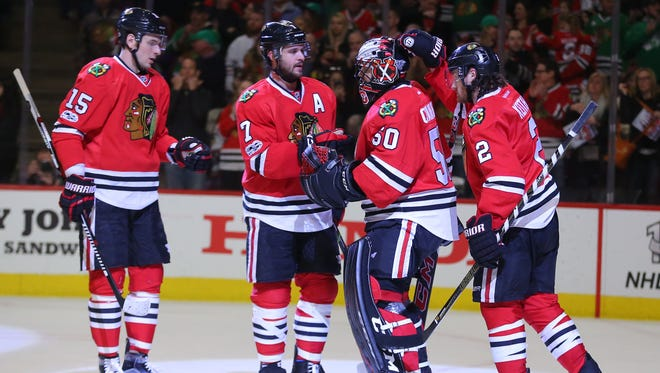 Chicago Blackhawks goalie Corey Crawford is congratulated by teammates after a 4-2 win against the Minnesota Wild.