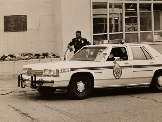 Officer Rainie Woods with his police cruiser. Woods was the first Black man to be a police officer in Bremerton.