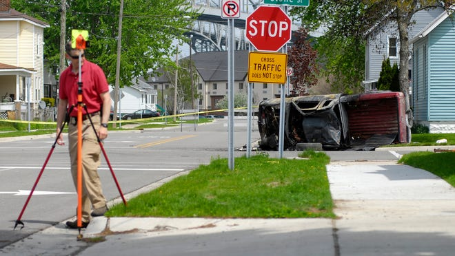 A vehicle is turned up on its side Monday, May 18, at the intersection of Harker and Stone Streets.
