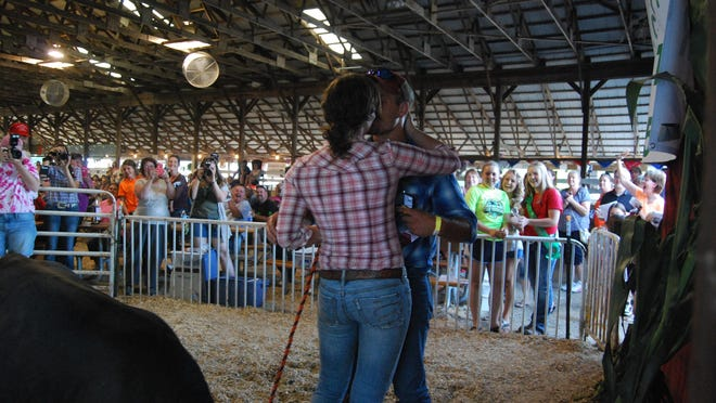 People applaud and take photos as Leah Simasko and Tommy Bolday embrace after he proposed Thursday at the St. Clair County 4-H Livestock Sale.