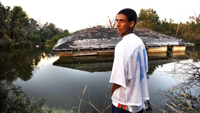 Maverick Ancar, a football player for Port Sulfur High School, looks at his home floating in a canal, Aug. 30, 2006.