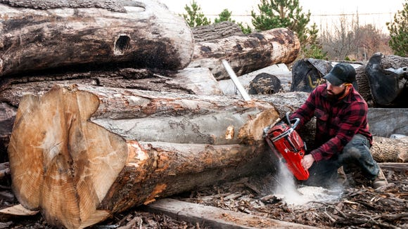 Forner Army SPC Anthony Fantauzzo trims a log to fit in the mill.
