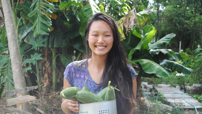 UCF student Hae-Yuan Chang with a batch of produce from the co-op garden she shares with seven roommates.