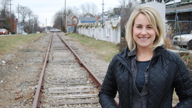 Susan Schaefer, president of the Wasson Way organization, stands next to a rail line at Wasson Road and Michigan Avenue. Cincinnati and the organization are looking at funding options to develop 7.6 miles of rail line into a hike and bike trail.