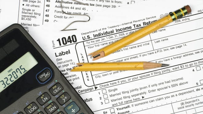 A tax form, calculator, broken pencil and bent paper clip show the frustration of filing taxes