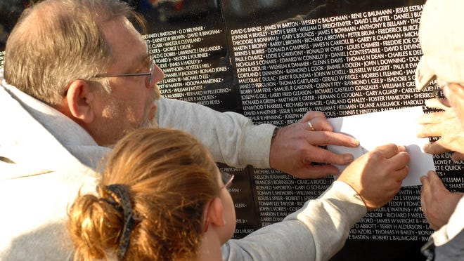 Don Andrews of Independence and his granddaughter Kylie Wells of Walton trace the name of a fallen soldier Andrews had served with in the Marines in the Vietnam War 1968-69.
