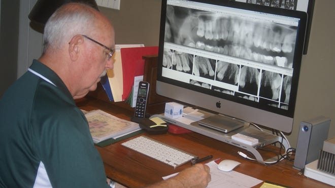 Dr. Richard Scanlon, a NamUs regional forensic odontologist, compares dental radiographs of missing and unidentified persons in hopes of securing a positive identification.