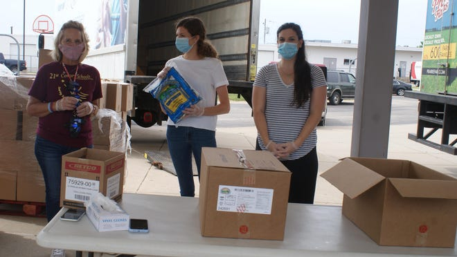 (From left) Cindy Long, Haley McClain and Kaitlyn Gudzinskas, all of Pekin, unpack boxes of food for distribution.