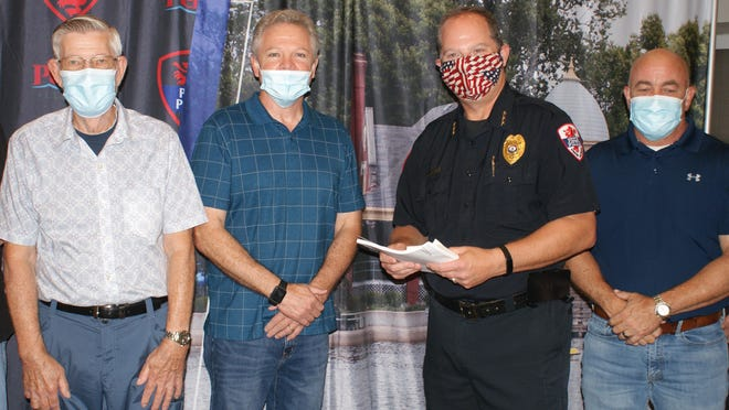 (From left) Calvary Baptist Church moderator Dale Vonderheide and senior pastor Rev. Mike McLeod present restaurant gift certificates to Pekin Police Chief John Dossey. Pekin Mayor Mark Luft was on hand for the presentation. [MIKE KRAMER/PEKIN DAILY TIMES}