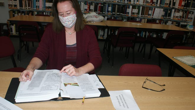 Tazewell County Genealogical and Historical Society President Susan Rynerson looks through a volume of local records. TCGHS recently won a Community Service Award from the Illinois State Genealogical Society.