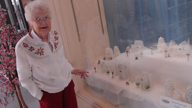 Suzanne Morris, 87, of St. Clair, looks at the winter village scene she crocheted for the window of Sweet Pea's Yarn and Gifts in St. Clair.