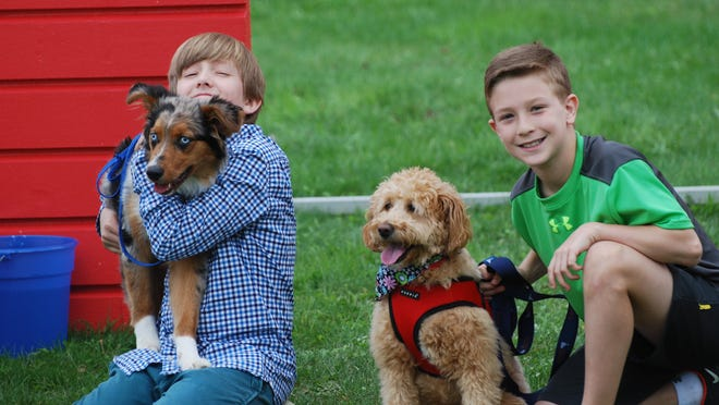 Above: Dutchess Day School sixth-graders William Leggat and Jacob Domber with their canine friends at the dog walk.  Left: Dutchess Day School eighth-grader Katherine Fousek and seventh- grader Phoebe Green commune with a canine pal.