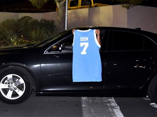 A driver displays a basketball jersey with Lamar Odom's name as the driver exits Sunrise Hospital and Medical Center on Tuesday, Oct. 13, 2015, in Las Vegas.
