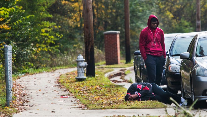 An unidentified man cries as he lies on the ground Wednesday, Dec. 7, 2016, as a supporter stands behind him on Overton Crossing Street following a fatal shooting in the 1900 block of The Oaks Ave. in Frayser on Wednesday. A female victim died at the scene and a male was discovered shot in the leg at the scene. He was transported to the hospital in noncritical condition.