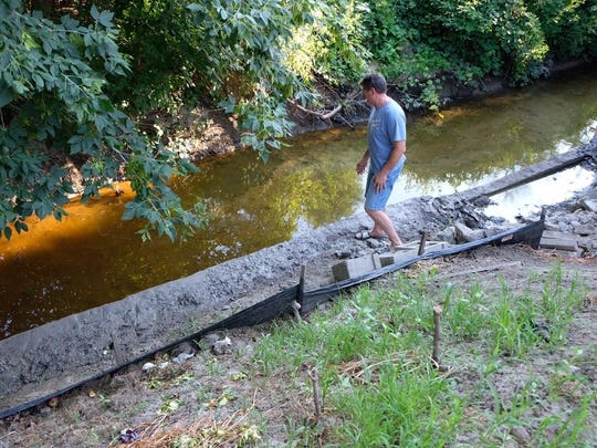 Tom Tailford looks at the Clinton River in his backyard.