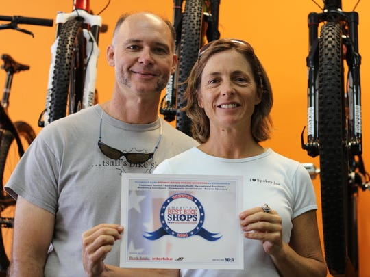 "Andy Zivinsky and Diane Cutler, owner of Bryson City Bicycles, show off their award as one of ""America's Top Bike Shops,"" named by the nonprofit National Bicycle Dealers Association."