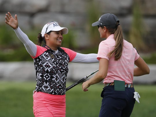 Jasmine Suwannapura of Thailand, left, hugs teammate Cydney Clanton on the 18th green after they won the Dow Great Lakes Bay Invitational golf tournament on Saturday in Midland.