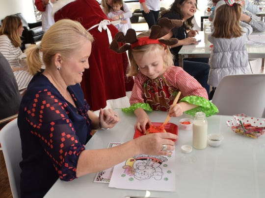 Lexie Pitre (left) helps niece Kinley Fitzgerald decorate a Christmas cookie at the annual Little Cakes with Big Attitude's Milk and Cookies with Santa held Saturday. Children were able to meet Santa Claus and Mrs. Claus, color, decorate cookies and have a picture session with Santa Claus.
