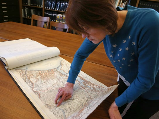 Christine Ridarsky, City Historian, looks over a paper