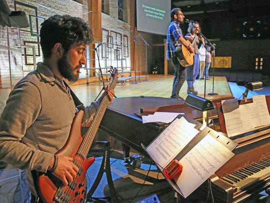 John Chabo plays bass during rehearsal as his brother, Michal, sings.  Michal Chabo, 26, and  John, 24, are Syrian refugees from Aleppo who came to Milwaukee two years ago. They've lived with a couple of families and now have their own apartment.