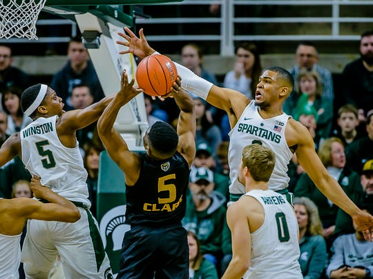 Alvin Ellis III ,top right, of MSU swats away a shot attempt by Stevie Clark ,center, of Oakland in the 1st half of their game Wednesday December 21, 2016 in East Lansing.  KEVIN W. FOWLER PHOTO