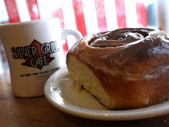 A cinnamon roll is paired with a hot cup of coffee